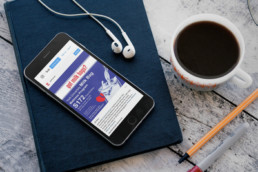 IPohone on top of a dark blue notebook with a pencil, cup of coffee and earphone surrounding it. On the screen is a graphic designed by Clivane Previlon