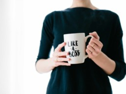 Woman-shows-her-personal-brand-as-she-holds-a-white-mug-that-says-Like-A-Boss